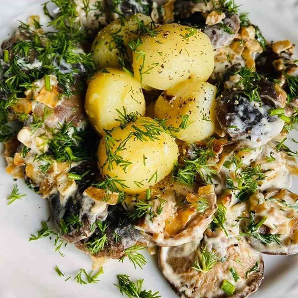 Keptuvėje troškinti miško grybai ir virtos bulvės su lupena