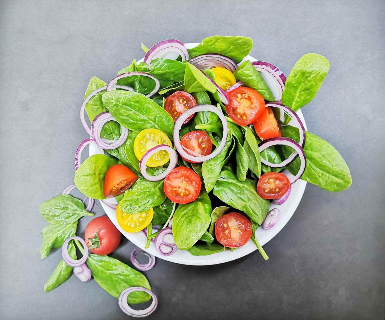 Špinatų salotos su pomidorais, mėlynaisiais svogūnais, moliūgų aliejumi